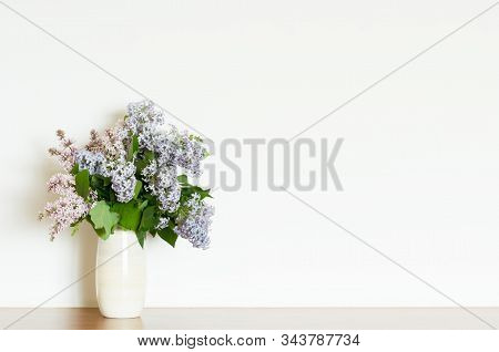 Home Decor, Lilac Flowers In Vase On A White Wall Background. Interior. - Image
