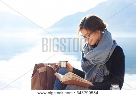 Young Woman Reading Book At Sea Beach. Cozy Winter Picnic By Morning Mountains. Happy Student In Blu