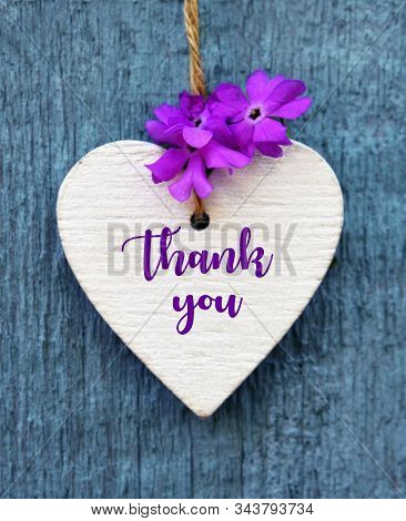 Thank You Or Thanks Greeting Card With Purple Flower And Decorative White Heart On Blue Wooden Backg