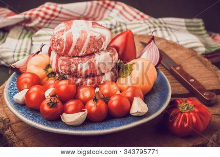 Meat Raw Round Cutlets Wrapped In Bacon And Vegetables Onion, Sweet Pepper, Garlic On A Blue Clay Pl