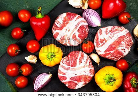 Meat Raw Round Cutlets Wrapped In Bacon And Vegetables Onion, Sweet Pepper, Garlic On A Black Stone