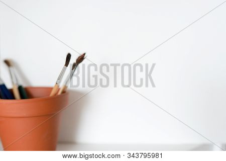 A Pot Of Artists Paint Brushes In A Browm Pot On A White Background. Copy Space Available.