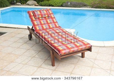 A Wooden Garden Deckchair Standing By The Pool