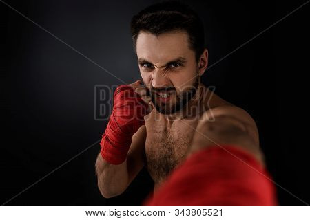 Sportsman Boxer Throwing A Fierce And Powerful Punch Forward In The Camera. Muscular Man With Red Ba