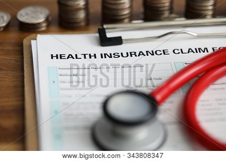 Close-up View Of Medical Reimbursement With Health Insurance Claim Form And Red Stethoscope On Table