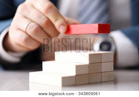 Close-up View Of Mans Hand Putting Red Unique Brick On Top Of Light Wooden Blocks. Metaphor To Manag