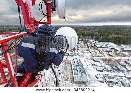 Professional Industrial Climber In Uniform And Climber Equipment On The Telecommunication Tower Is I
