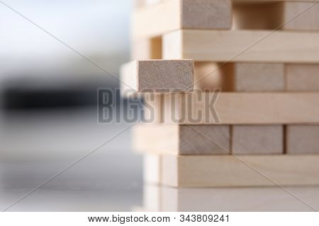 Close-up View Of Wooden Blocks Tower. Metaphor To Vulnerable Situation. Selective Focus On Unpainted