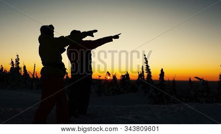 People Silhouettes Admire Pictorial Sunset And Raise Hands