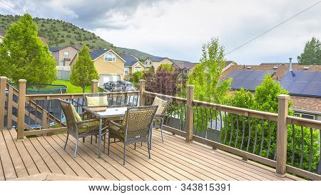 Pano Deck Overlooking Solar Panels On Roof Of Home Against Mountain And Cloudy Sky