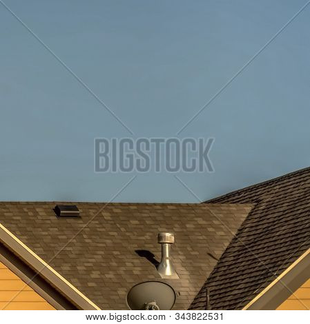 Square House Exterior With Roof Shingles And Round Gable Window Against Blue Sky