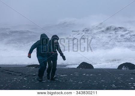 A Loving Couple Is Walking Along The Shore Of A Raging Ocean. Long Exposure. Valentine's Day. In Dis
