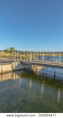 Vertical Frame Bridge Over Lake With Lakefront Buildings And Mountain View Under Blue Sky
