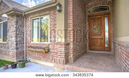 Pano Brick House With Arched Entrance Leading To Front Door With Sidelight And Wreath
