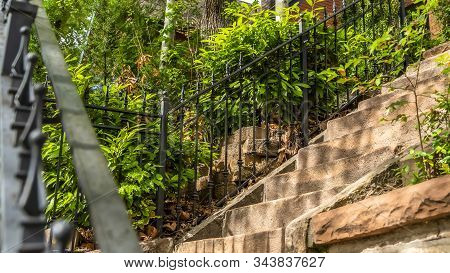 Pano Frame Sunlit Stone Stairway With Black Metal Railing And Brick House Background