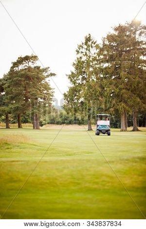 Front View Of Couple Playing Golf Driving Buggy Along Fairway On Red Letter Day