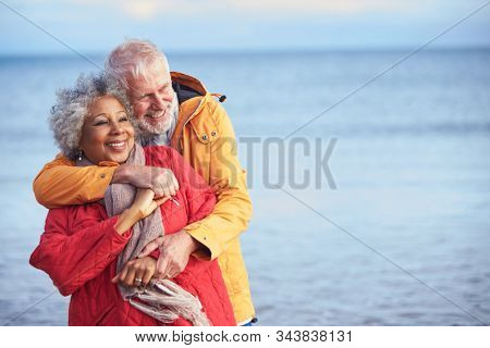Loving Senior Couple Hugging As They Walk Along Shoreline On Winter Beach Vacation