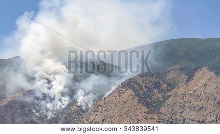 Pano Frame Mountain Landscape With Smoke From Wild Forest Fire Against Clear Blue Sky