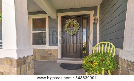 Pano Frame Porch And Facade Of Home Decorated With Colorful Flowers And Wreath On The Door