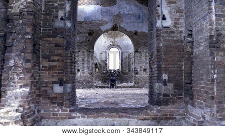 Man In A Wheelchair In A Ruined Church. Footage. Back View Of A Man In An Abandoned Church. The Conc