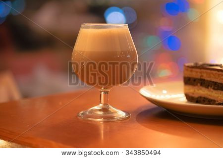 Glasse Of Coffee Liqueur Cocktail On Soft Blurred Background With Colorful Streetlights And A Cake.