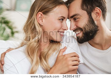 Close up of a beautiful happy young couple in love embracing at home, embracing