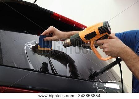 Worker Tinting Car Window With Heat Gun In Workshop, Closeup