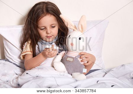 Little Girl Lying In Bed And Measuring Soft Hear's Temperature With Thermometer, Child Lying In Bed