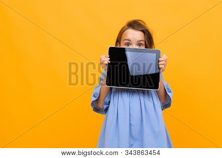 Charming Attractive Caucasian Girl In Dress Shows Tablet Display On Bright Yellow Background.