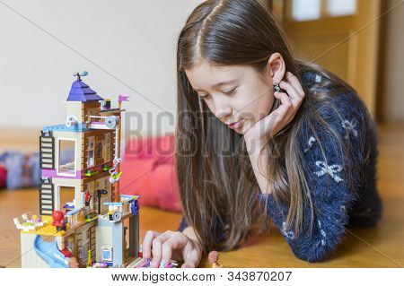 Little Girl Plays With A Childrens Constructor At Home. Little Girl Playing With Lots Of Colorful Pl