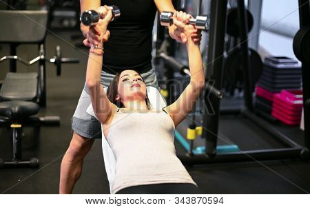 Woman training her chest with the help of her personal trainer