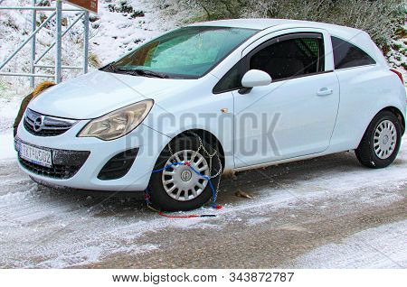 Meteora, Greece-december 30, 2019: Driver Of White Opel Corsa Is Trying To Mount Snow Chains On His