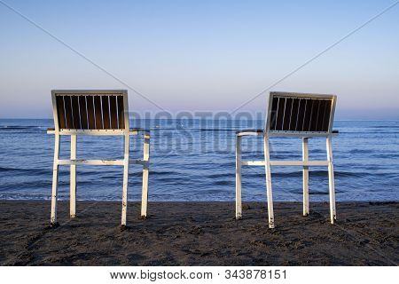 Two Empty Chairs Stand On Beach In Evening With View On Marine Sunset.chairs Stand In The Sand.