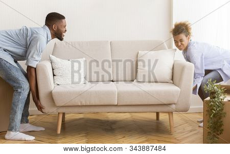 Moving House. African American Spouses Lifting Heavy Couch Furnishing Empty Room After Relocation In