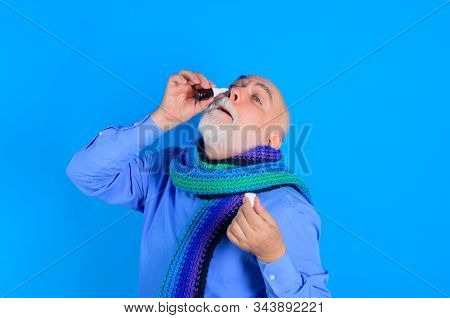 Treatment For Allergies Or Common Cold. Senior Man Using Nasal Spray. Bearded Man Uses Spray Drops O