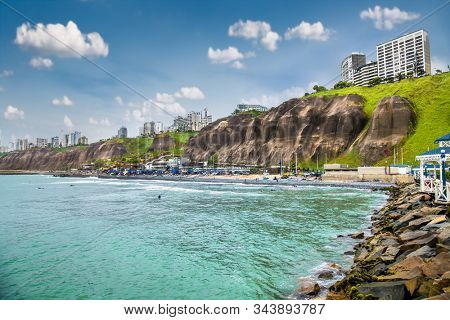 Pacific coast view in sunny day, observation deck, stairway to the beach. View from the Public park in Miraflores district. Lima, Peru.