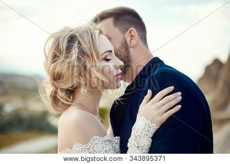 Couple In Love Hugs And Kisses In Fabulous Mountains In Nature. Girl In Long White Dress With Bouque