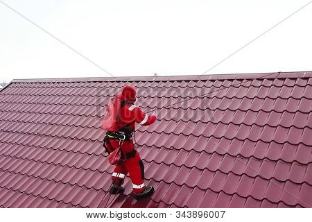Worker Does The Installation Of The Roof Of The House. Installation Of Metal Tiles, Snow Retainers A