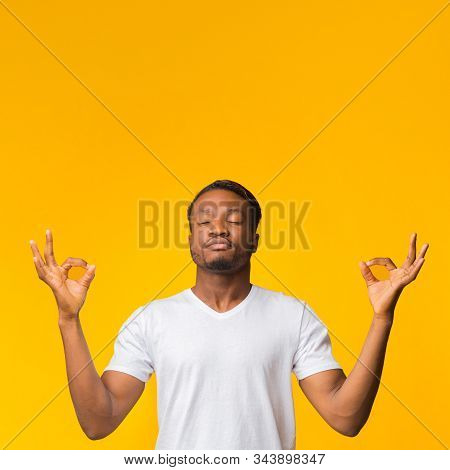 Keep Calm. Zen-like Afro Guy Meditating Standing Over Yellow Background. Studio Shot, Copy Space