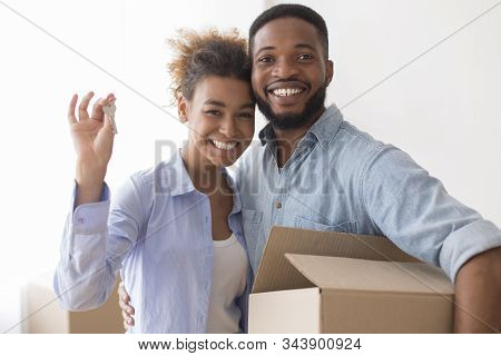 Own Home. Young Afro Spouses Showing New House Key Hugging And Holding Moving Box Standing Indoor.