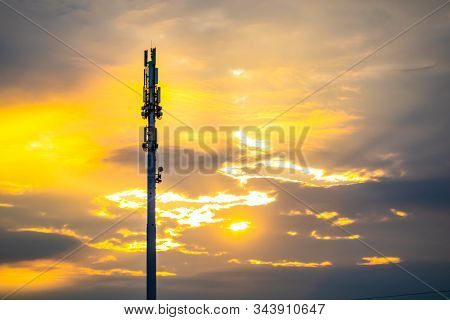 A Wide Angle View Of A Monopole Cell Site Tower At Sunset. Golden Backlit Silhouetted Cellular Base