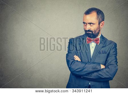 Jealousy, Envious. Serious Adult Gloomy Bearded Man In Elegant Suit With Red Bow Tie On Gray Backgro
