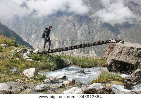 Summer Hiking In Cordillera Mountains: Hiker Crosses The River In The Mountains, Outdoor Adventure C