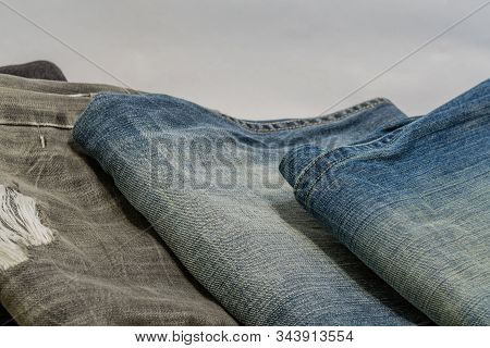 Closeup Of Three Pairs Of Denim Jeans On White Background.