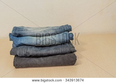 Closeup Of Four Pairs Of Denim Jeans Folded Neatly On Wood Grain Table Top,