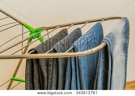 Closeup Of Four Pairs Of Denim Jeans Hanging Neatly On Fordable Drying Rack.