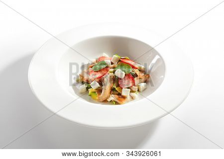 Salad with smoked eel fish, avocado, feta cheese and strawberries on restaurant plate isolated. Delicious luxury seafood salat with unagi, broccoli and nasturtium leaves closeup