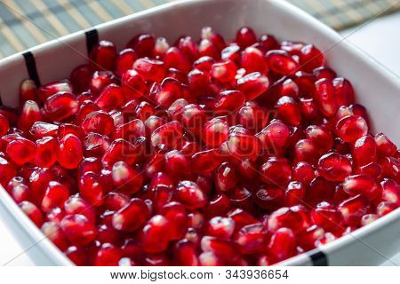 Red Ripe Delicious Juicy Pomegranate Seeds In A Plate