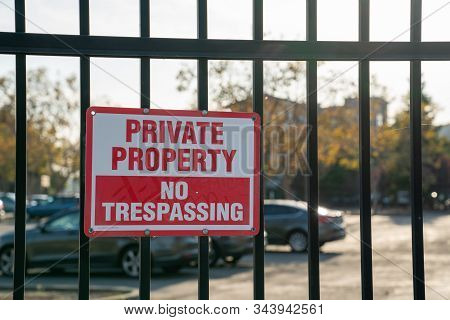 Private Property No Trespassing Sign On Black Gate In Front Of A Parking Lot