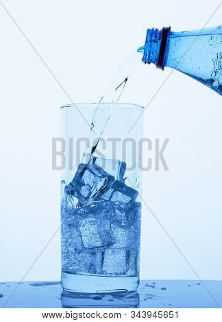 Clean Drinking Mineral Water From A Bottle Is Poured Into A Glass With Ice